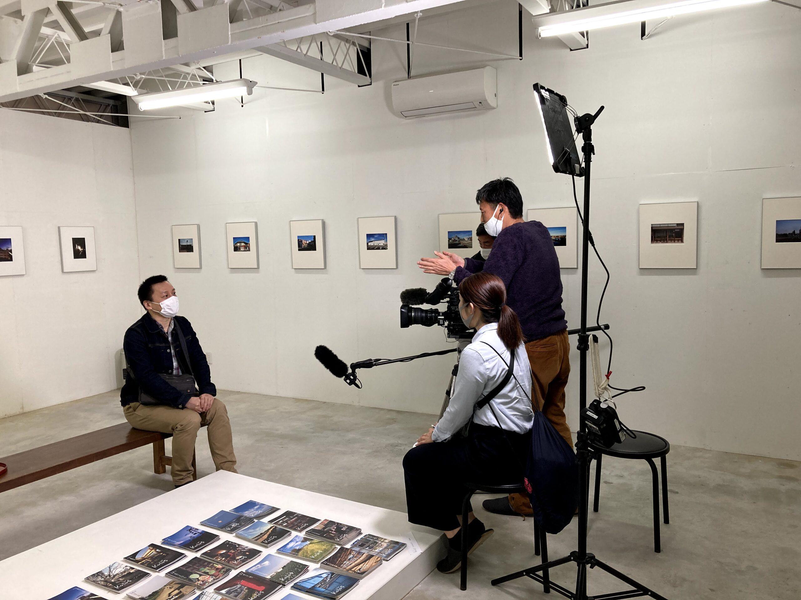 2021界隈Ⅱ写真展 NHK津放送局のインタビューを受けるkalasbooks西屋さん